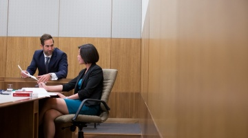 Two people dressed in suits consulting at desk